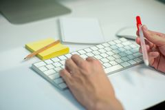 Selective focus on white keyboard of desk top with blurred motion of hands spinning the pencil in foreground with notepad and royalty free stock image