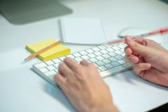 Selective focus on white keyboard of desk top with blurred motion of hands spinning the pencil in foreground with notepad and royalty free stock photos
