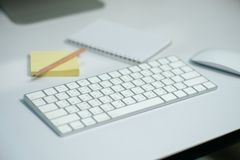 Selective focus on white keyboard on the desk with defocused stationary, and mouse in background royalty free stock photos