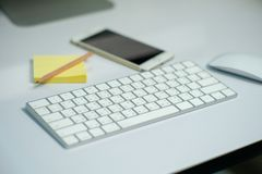 Selective focus on white keyboard on the desk with defocused stationary, mouse, and mobile phone in background stock photography