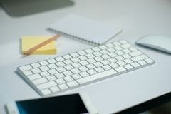 Selective focus on white keyboard on the desk with defocused stationary, mouse, and mobile phone in background stock photos