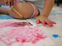 A white plain paper being painted by a little baby using a small brush. Selective focus of a white plain paper being painted by a little baby using a small brush stock photo