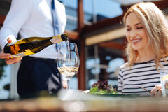 Selective focus of wine being poured in a glass. Excellent choice. Selective focus of white semisweet wine being poured into a glass by a nice skillful handsome Stock Photo