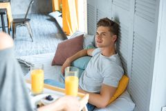 Selective focus of woman brought breakfast to caucasian boyfriend. In bed at home stock image