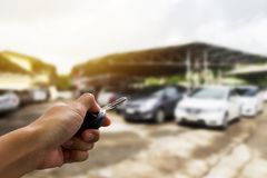 Selective focus of woman hand presses on the remote control car. Alarm systems with defocused and blur image of car park in outdoor. Auto insurance business stock image