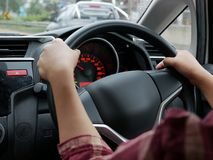 Woman hand on steering wheel driving a car with both hands. Selective focus of woman hand on steering wheel driving a car with both hands stock photo