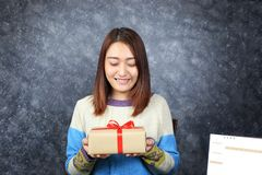 Selective focus of Woman hands holding gift box with red ribbon royalty free stock image