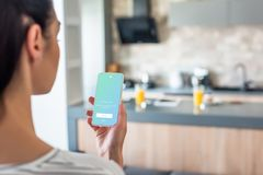 Selective focus of woman holding smartphone with twitter logo on screen. In kitchen stock image