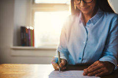 Selective focus of woman working at home office. Selective focus on hands of single woman in blue blouse working at desk on paperwork in home office with Stock Images