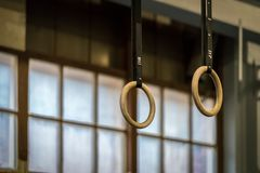 Selective focus of wooden gymnastic rings in front of a large window. Horizontal composition Royalty Free Stock Photos