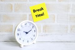 Selective focus of yellow sticky notes written with 'BREAK TIME!' with and table clock.  royalty free stock image