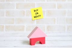 Selective focus of yellow sticky notes written with BUY OR RENT? with house toys on white wooden background. Real estate theme.  stock photo