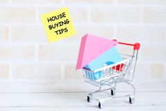 House buying tips. Selective focus of yellow sticky notes written with HOUSE BUYING TIPS with house model and trolley or a shopping cart on white wooden Stock Photos