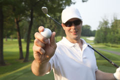 Selective focus of a young male golfer holding golf ball out in Stock Images