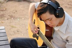 Selective focus of young relaxed man is playing acoustic guitar in outdoor. Stock Photo
