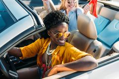 Selective focus of young stylish african american woman. Selective focus of young stylish african american women riding car with friend stock image