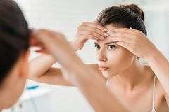 Selective focus of young woman. Checking facial skin and looking at mirror in bathroom stock photo