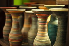 Selective focused closeup multicolored colorful traditional clay sculpture spiral flower vases on the wooden shelf royalty free stock photos
