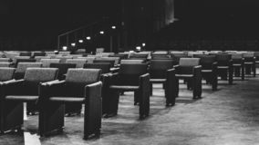 Selective perspective view towards empty audience seat in an indoor performance hall or cinema royalty free stock photos