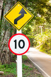Selective speed limit traffic sign 10 and winding road caution symbol for safety drive in country road Royalty Free Stock Image