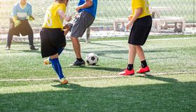Selective to kid soccer player and coach are training and fighting to shoot ball and charges kid goalkeeper royalty free stock images