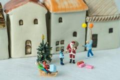 Selectivo centrado en la figura miniatura Papá Noel que da el presente Imagen de archivo libre de regalías