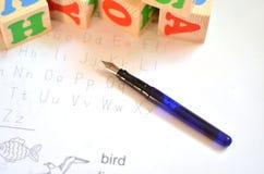 Selekcyjna ostrość angielszczyzna listy z piórem odizolowywa na białym tle dla nauk angielszczyzn pojęcia 3 d listów kostek Obrazy Royalty Free