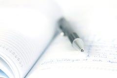 Selekcyjna ostrość balowy pióro na rozpieczętowanej prążkowanej dzienniczek książce Fotografia Stock