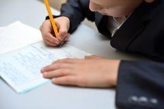 Selekcyjna ostrość chłopiec uczenie dlaczego pisać jego imieniu, dzieciak nauka w domu, dzieci robi pracie domowej w domu, pojęci obrazy stock
