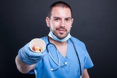 Selekcyjna ostrość jest ubranym pętaczki pokazuje filiżankę z pigułkami lekarka Obrazy Royalty Free