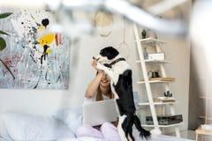 selekcyjna ostrość kobieta w piżamach bawić się z szczeniakiem w ranku obrazy royalty free