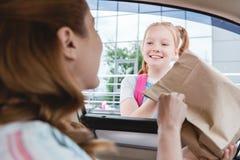 selekcyjna ostrość kobieta w samochodowym daje papierowym pakunku z jedzeniem obrazy stock