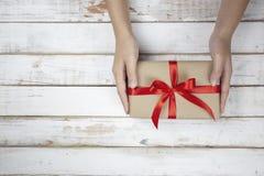 Selekcyjna ostrość kobieta wręcza mienie prezenta pudełko z czerwonym faborkiem fotografia stock