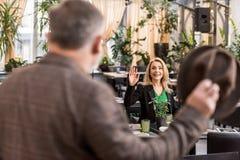 selekcyjna ostrość kobiety falowanie obsługiwać podczas gdy siedzący przy stołem zdjęcia royalty free