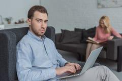 selekcyjna ostrość mężczyzna z laptopem i macierzystymi patrzeje fotografiami w albumu fotograficznym na kanapie zdjęcia royalty free