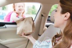 selekcyjna ostrość matka w samochodowym daje papierowym pakunku z jedzeniem fotografia royalty free