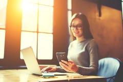 Selekcyjna ostrość na nowożytnym telefonie komórkowym holded uśmiechniętym żeńskim freelancer zdjęcia stock