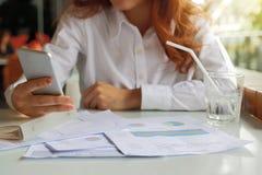 Selekcyjna ostrość na rękach biznesowej kobiety mienia telefon komórkowy dla jej pracy w biurze Obrazy Stock