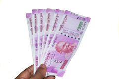 Selekcyjna ostrość: Ręki mienia indianin 2000 rupii notatek przeciw białemu tłu Zamyka w górę nowego rupia 2000 banknotu na mężcz zdjęcia stock