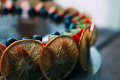 Selekcyjnej ostrości czekoladowy tort z pomarańczami i jagodami obraz stock