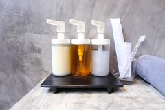 Selekcyjny focuse Pompowa szklana butelka z Ciekłym mydłem, szamponem, skąpanie pianą i akcesoriami w łazience przy luksusowym ho zdjęcia stock