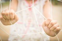 Selektiv för flickainnehav netto och mjuk fokus arkivbilder