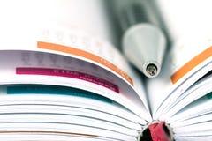 Selektiv fokus av bollpennan på den öppnade fodrade dagbokboken med cale arkivbild