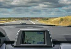 Selektiv fokus av byggt i GPS navigatören på instrumentbrädan av en bil som går ner den sceniska huvudvägen i Algarve, Portugal royaltyfri bild