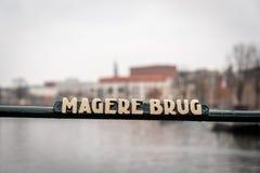 Selektiv fokus av en brostålstång med ett tecken av den berömda Mageren Brug i Amsterdam royaltyfri bild