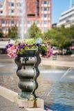 Selektiv fokus av en stor bronsvas med färgrika blommor på en stadsfyrkant med vattenspringbrunnen och byggnader arkivbild