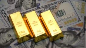 Selektiv fokus av guld- stänger och dollar på en tabell lager videofilmer