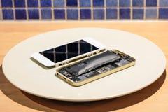 Selektiv fokus av inom ett skadat brutet och däst mobiltelefonbatteri med lös skärm bredvid arkivbilder