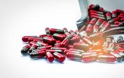 Selektiv fokus för makroskottdetalj av röda och gråa kapselpreventivpillerar som isoleras på rostfritt ståldrogmagasinet Migränpr royaltyfri foto