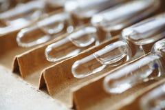 Selektiv fokus med perspektivsikt av många glass ampuller eller små medicinflaskor i farmaceutiskt förpacka royaltyfri foto